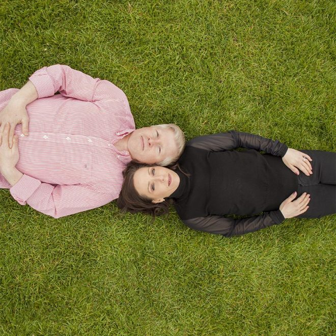A couple relaxes on the grass