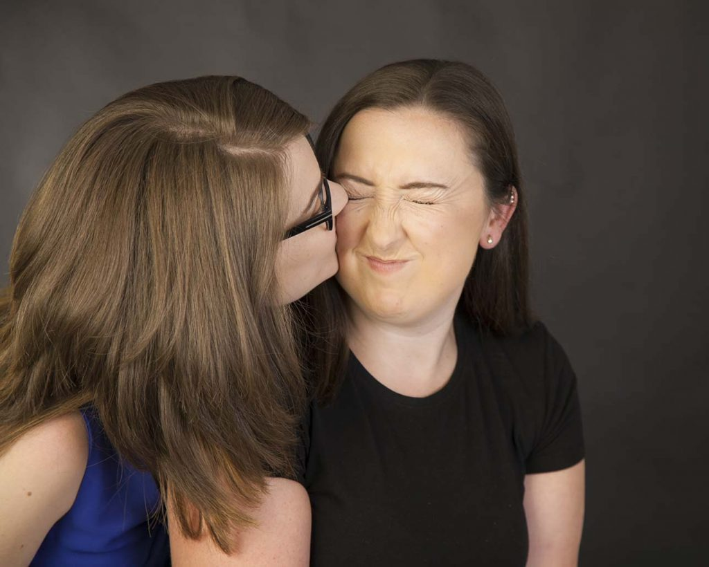 sister gives a kiss to an face